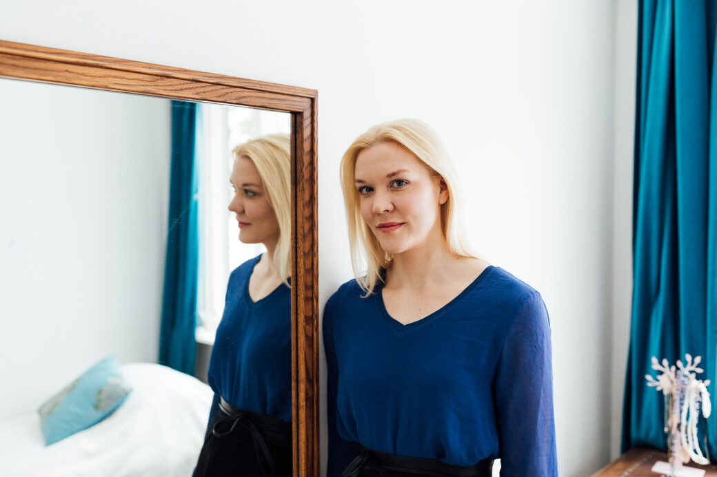 Blond haired woman in a blue top standing sideways to a mirror.