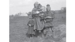 Archive image of a Sámi woman with a baby in her arms and two children standing next to her
