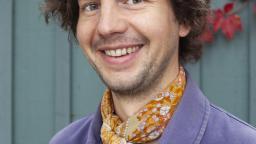 Oskar Kroon in yellow scarf and purple blazer
