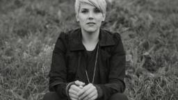 Andrea Lundgren sitting in grassy meadow.