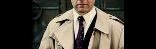 Carl-Michael Edenborg in a suit and trenchcoat